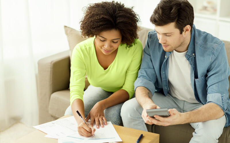 couple sitting on couch planning their budget